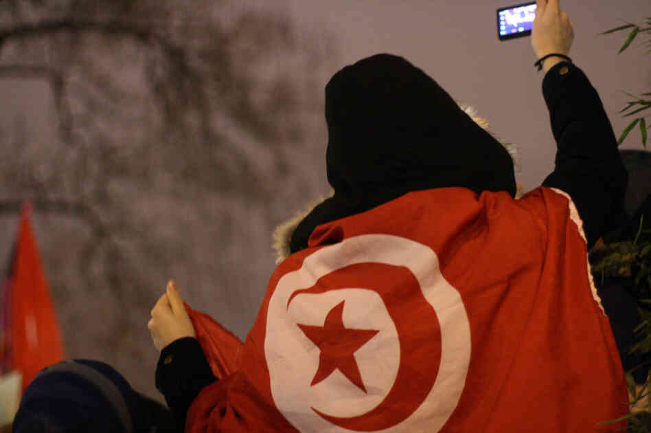 A woman uses her mobile phone to take a picture of a rally in Paris in support of protesters in Tunisia.