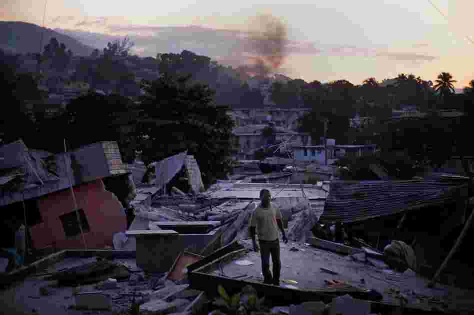 A man stands on a roof top overlooking the destruction in Port-au-Prince, Jan. 15, 2010.