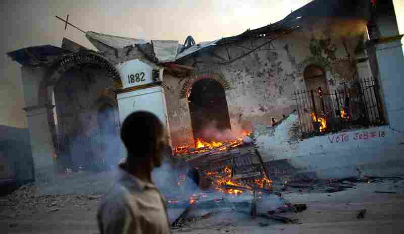 A man walks past a burning church near a destroyed Catholic church in downtown Port-au-Prince, Jan. 18, 2010.
