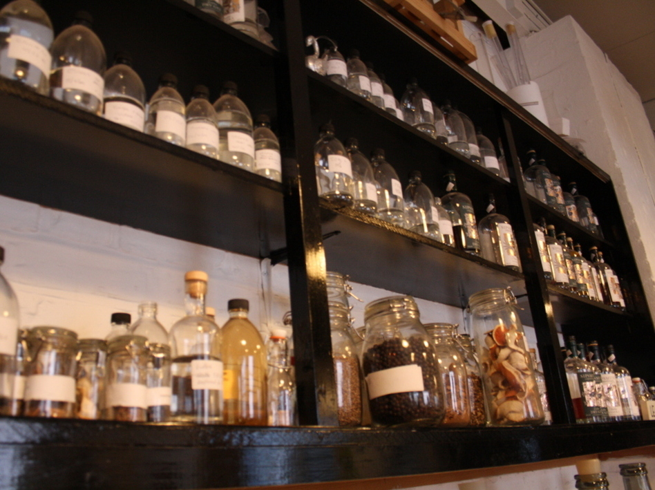 Jars of spices sit along a shelf, waiting to flavor Sipsmith's gin. (NPR)