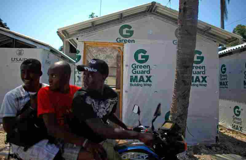 Four months after the earthquake, a group of Haitians ride by one of the pre-fabricated houses being built for people in Leogone, Haiti. The houses are a temporary solution to the long-term problem of rebuilding, May, 2010.