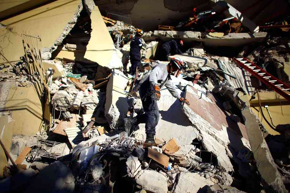 A rescue team from south Florida tries to reach survivors in a collapsed supermarket near downtown Port-au-Prince, Jan. 16, 2010.