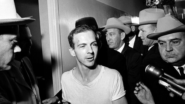 Surrounded by detectives, Lee Harvey Oswald talks to the press as he is led down a corridor of the Dallas police station after the assassination of U.S. President John F. Kennedy.
