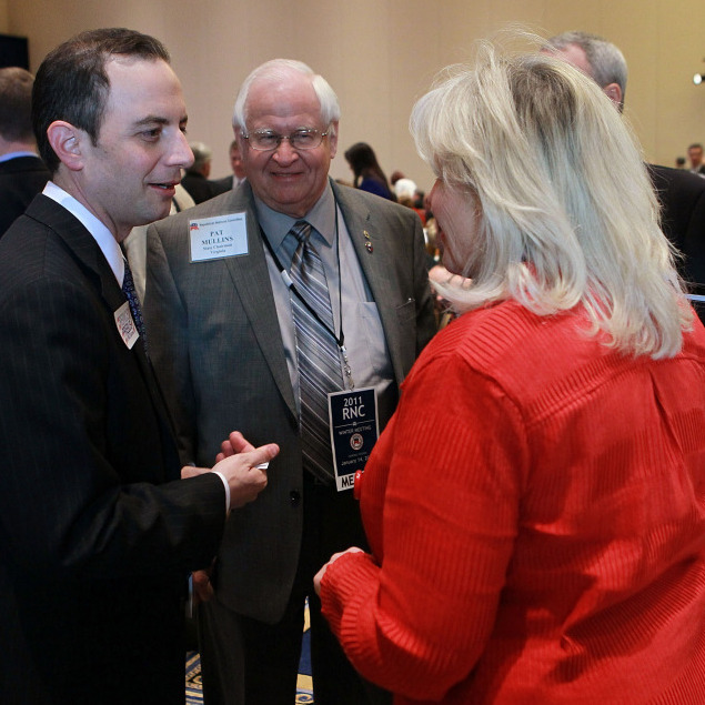 Wisconsin state party chairman Reince Priebus (L), a candidate for the Republican National Committee chairman, talks with RNC meeting attendees.