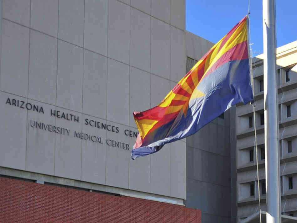 The flag of the state of Arizona flies at half-staff outside University Medical Center in Tucson, Ariz., on Jan. 8.
