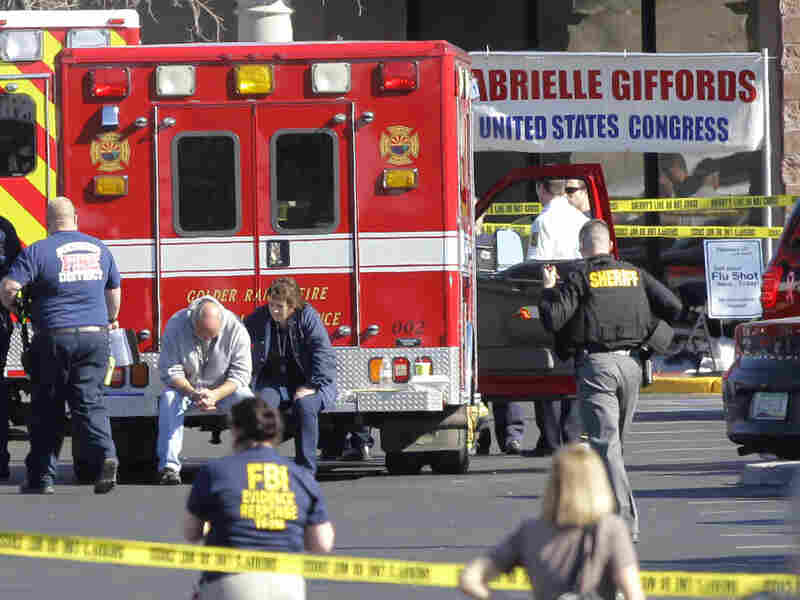 Emergency personnel work on Jan 8 at the scene where Rep. Gabrielle Giffords, (D-AZ) and others were shot outside a Safeway grocery store in Tucson, Ariz. Nearly anyone at the scene that day will be at risk for post traumatic stress disorder, but it's difficult to predict who will be affected.