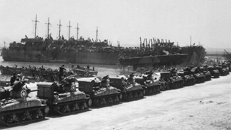 Tanks line up to board landing ships at the French Naval Base in Tunisia, July 1943.