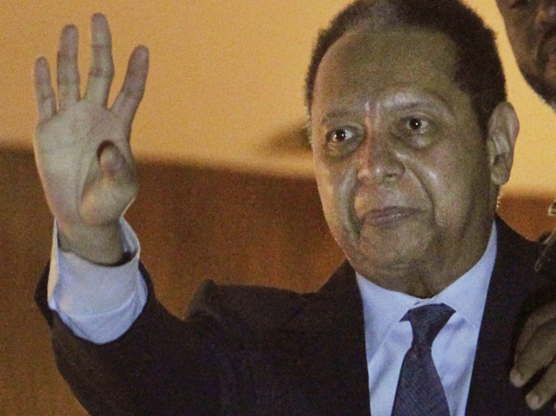 "Former president of Haiti Jean-Claude ""Baby Doc"" Duvalier waves to supporters from a hotel balcony Sunday after his arrival in Port-au-Prince. Duvalier returned to the country after nearly 25 years in exile."