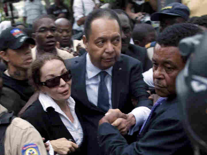 Former president of Haiti Jean-Claude Duvalier (center) and his longtime companion, Veronique Roy, leave court Tuesday in Port-au-Prince.