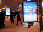 "People walk past posters reading in Estonian ""Euro is our money."""