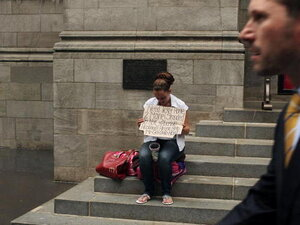 A business man walks by a homeless woman holding a card requesting money in New York City. A new report released by the U.S. Census Data shows that the income gap between Americans is greater than at any other time on record.
