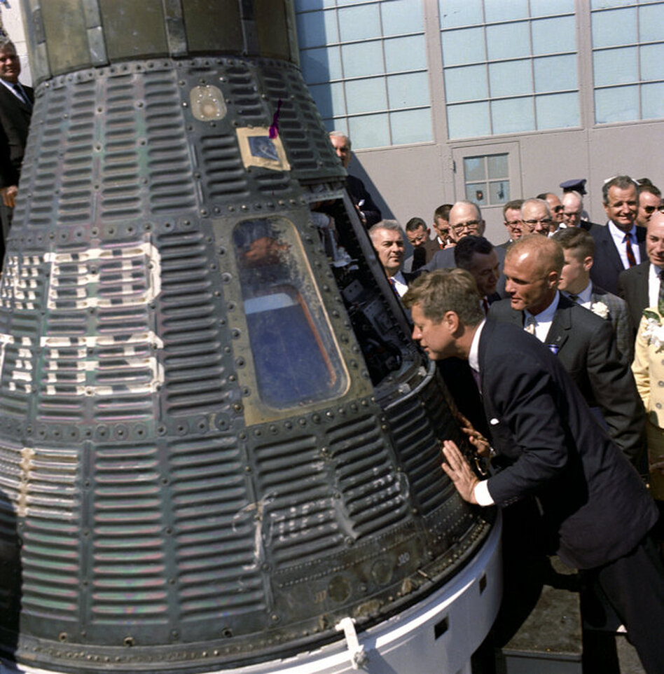 President Kennedy gets a look inside the Mercury capsule that was piloted by John Glenn (at Kennedy's right) on Feb. 23, 1962.   (John F. Kennedy Presidential Library/NPR)