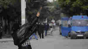 A demonstrator throws a rock towards police during demonstrations in Tunis.