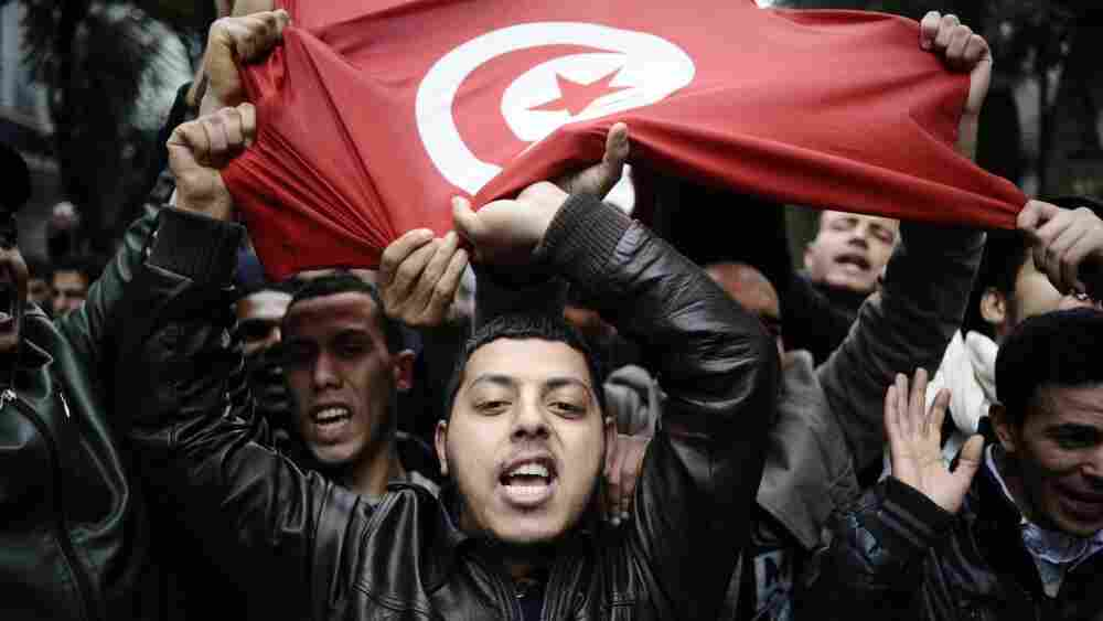 Protesters hold up a Tunisian flag during a demonstration in the streets of Tunis on Tuesday.