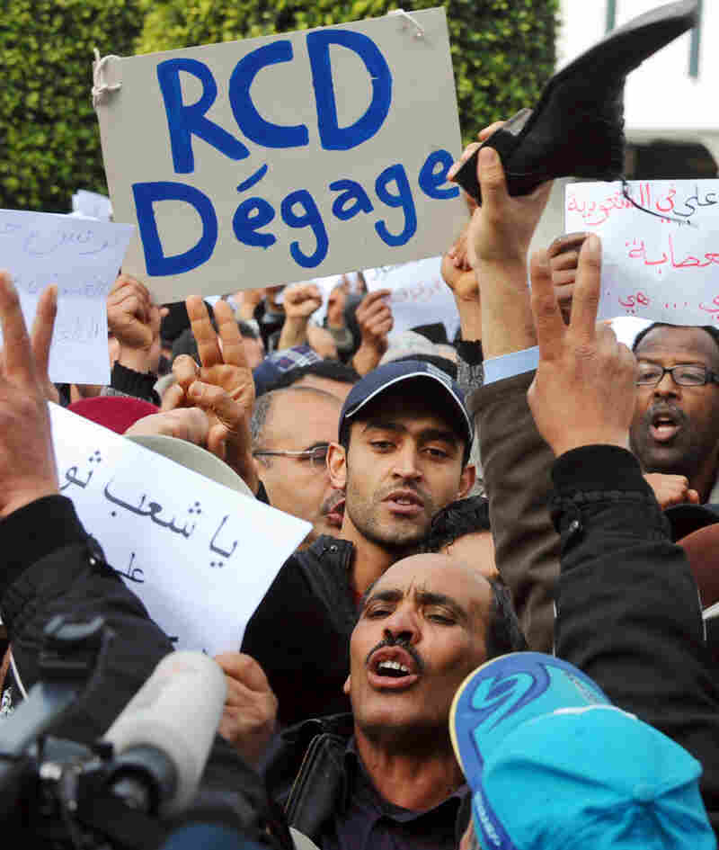"""Protesters hold signs reading """"RCD Get Out"""" at a march in Tunis on Wednesday."""