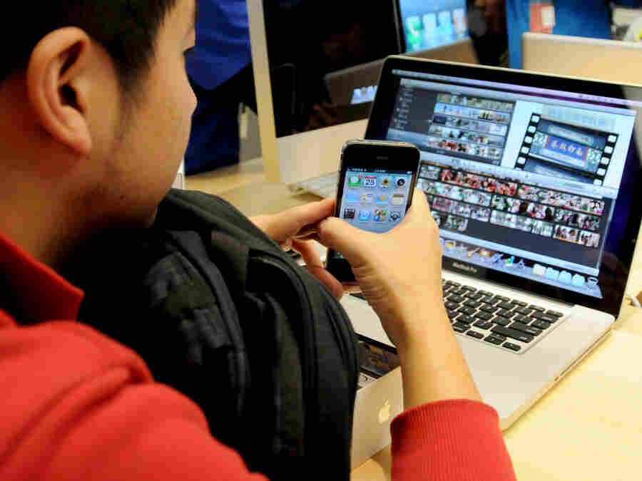 A Chinese customer checks out his newly purchased iPhone 4 at Apple's flagship store in Beijing. Mobile Internet use in China topped 300 million people in 2010.