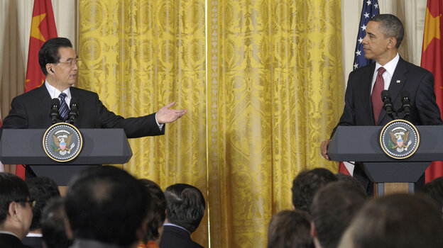 China's President Hu Jintao gestures toward President Obama during their joint news conference, Wednesday in the East Room of the White House.