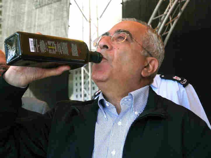 Palestinian prime minister Salam Fayyad tastes freshly pressed and bottled olive oil in Bethlehem.