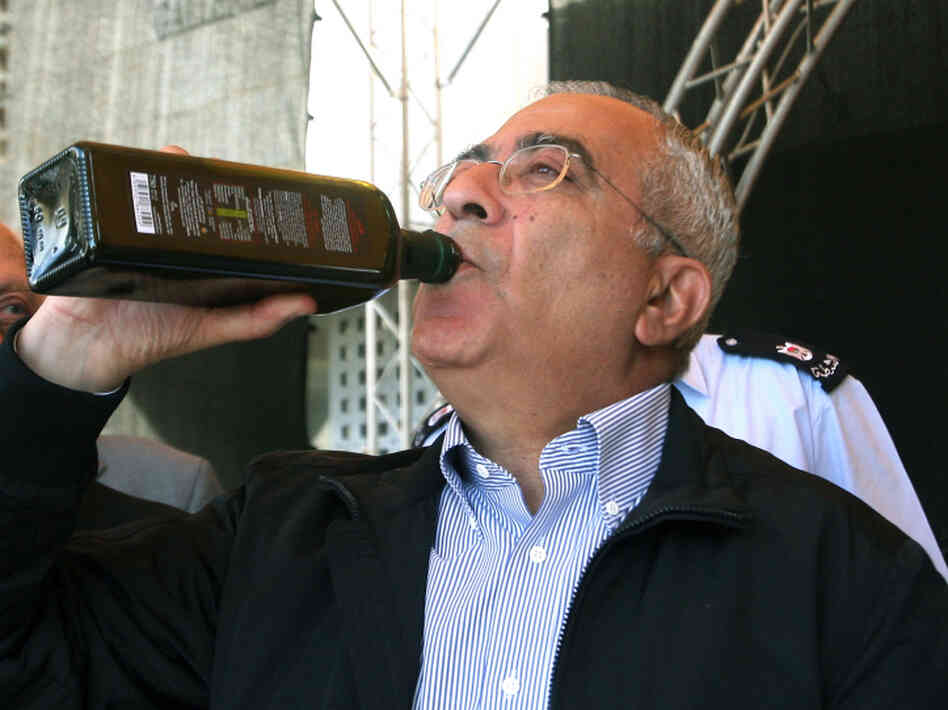 Palestinian prime minister Salam Fayyad tastes freshly pressed and bottled olive oil in Bethlehem.