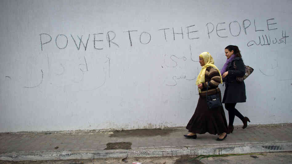 Two women walk past graffitti scrawled on a wall surrounding the burnt and looted house that belonged to the nephew of ousted Tunisian President Zine El Abidine Ben Ali in Hammamet, southeast of Tunis.