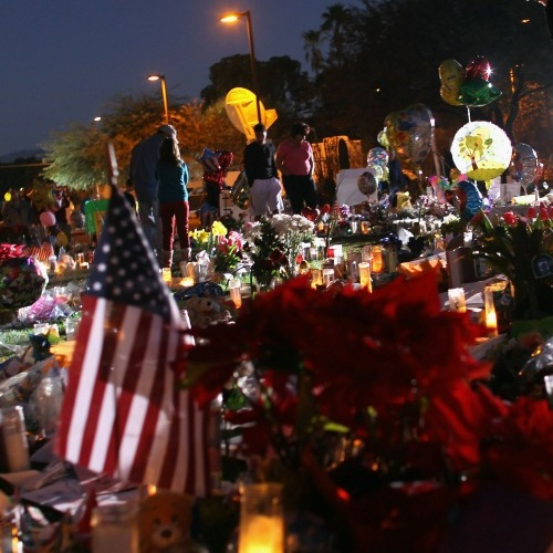Teri Baffert looks items at the impromptu memorial outside the University Medical Center in Tucson, Arizona.