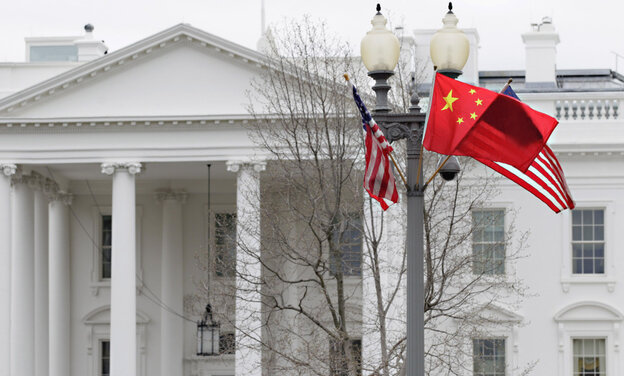 American and Chinese flags fly in front of the White House as Chinese President Hu Jintao arrives for a state visit.