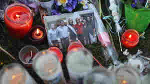 A makeshift memorial outside the University Medical Center in Tucson includes candles and this photo of Rep. Gabrielle Giffords with supporters.