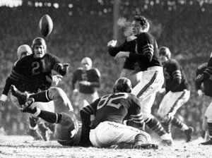 In the 1941 Western Division playoff game at Wrigley Field, Chicago Bears guard Danny Fortmann (21) gets a bead on the ball jarred loose by Bears guard Ray Bray (82).