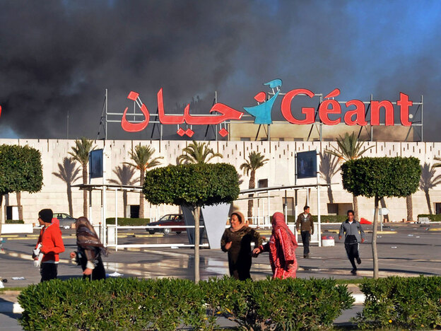 A supermarket smolders after it was sacked and looted in Bizerte, Tunisia, on Jan. 15. Despite the continuation of random attacks by forces loyal to the country's former president, residents of the northern port city say they are striving to get on with their lives.