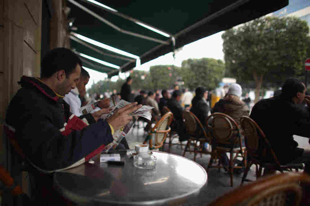 A Tunisian man reads a newspaper at a cafe in Tunis on Thursday. The press was censored during Zine El Abidine Ben Ali's 23-year rule. That changed overnight last Friday when he and his wife fled the country.