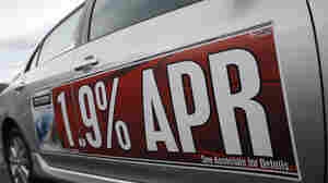 A low-interest rate banner hangs on the side of an unsold 2010 Toyota Corolla at a dealership in Lakewood, Colo.