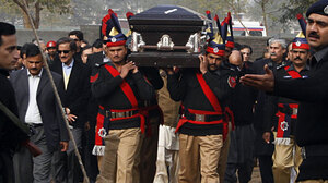 Pakistani police guards carry the coffin of the assassinated governor of Punjab, Salman Taseer, during the funeral procession in Lahore on Jan. 5.