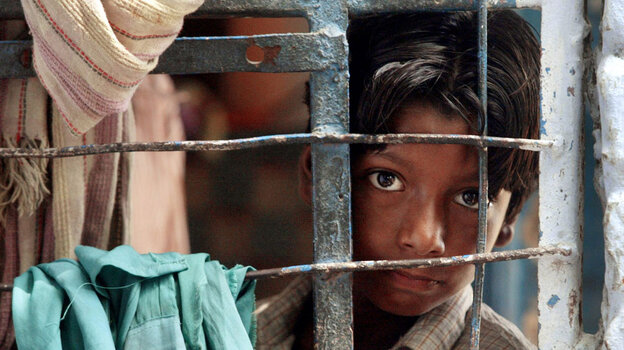 A street child looks out from his classroom during studies conducted by the Salaam Baalak Trust at the New Delhi railway station in September 2004. Salaam Baalak Trust is an Indian charity for homeless children.