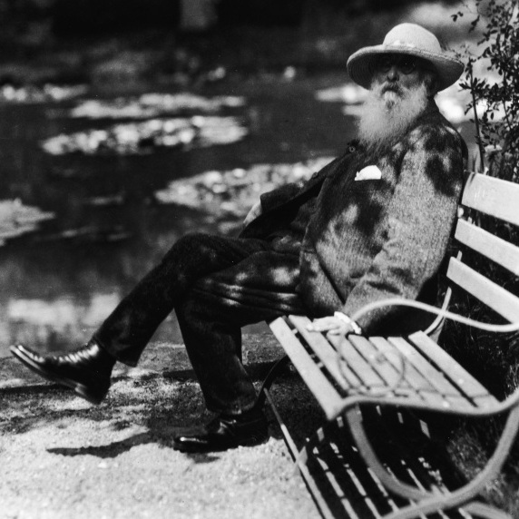 French impressionist painter Claude Monet sits beside the water lily pond in his home garden in Giverny, France, circa 1910.