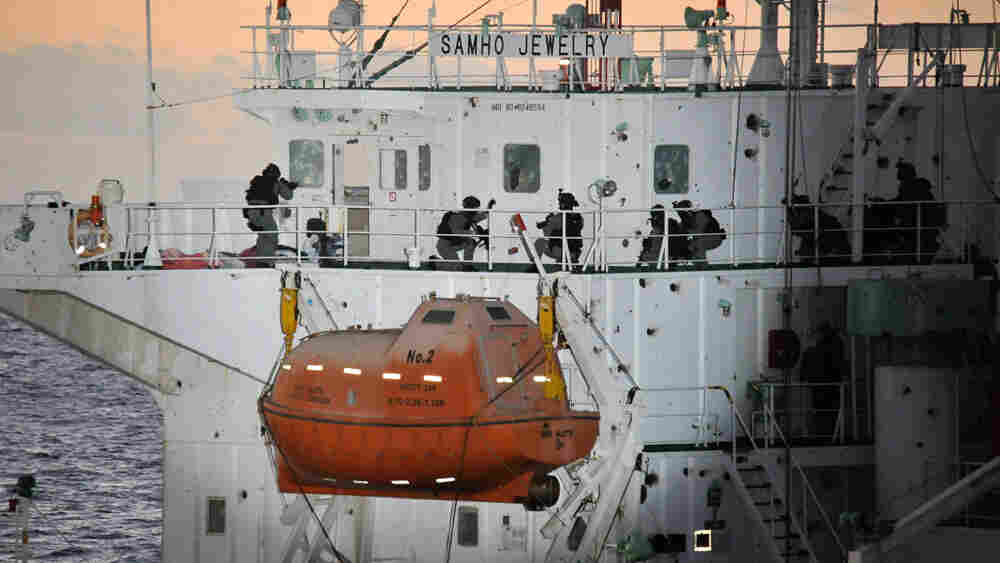 Members of South Korean naval forces board the hijacked cargo ship Samho Jewelry to rescue crew members on Friday in the Arabian Sea.