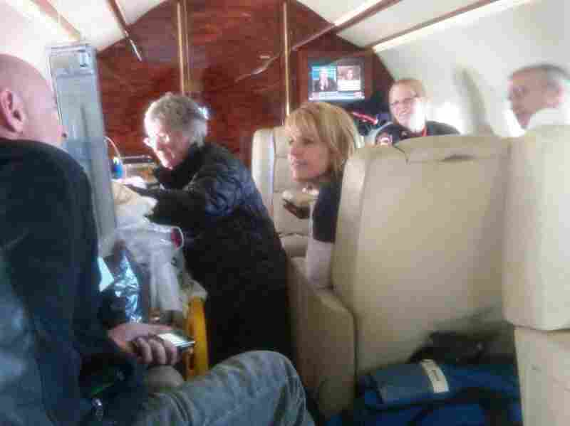 Gloria Giffords (center), Rep. Gabrielle Giffords' mother, talks with her daughter on the flight to Houston. Capt. Mark Kelly (far left), the representative's husband, talks with Tracy Culbert (center right), a nurse.