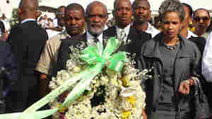 Haitian President Rene Preval (center) prepares to lay a wreath on Jan. 11 at St. Christophe in Port-au-Prince, where thousands of victims of the Jan. 12, 2010, earthquake are buried.