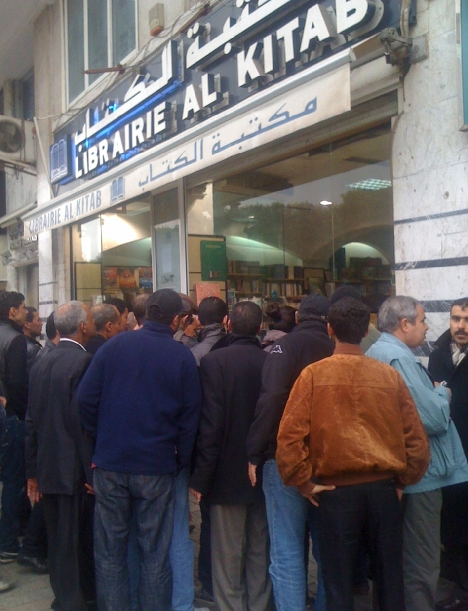 A crowd looks through the window of a Tunis bookstore at books that were previously banned.