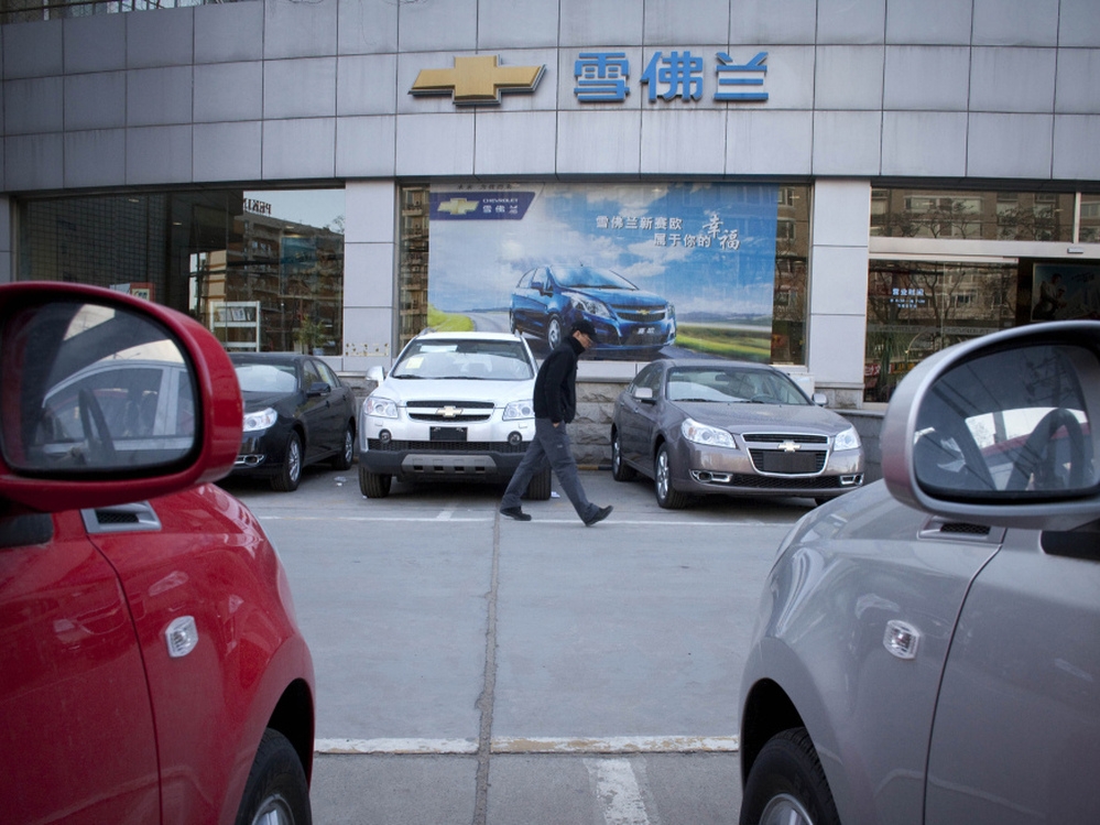 A man walks outside a Chevrolet dealership in Beijing. Despite GM's sales surge in China in 2010, Toyota held onto the title of world's largest automaker.