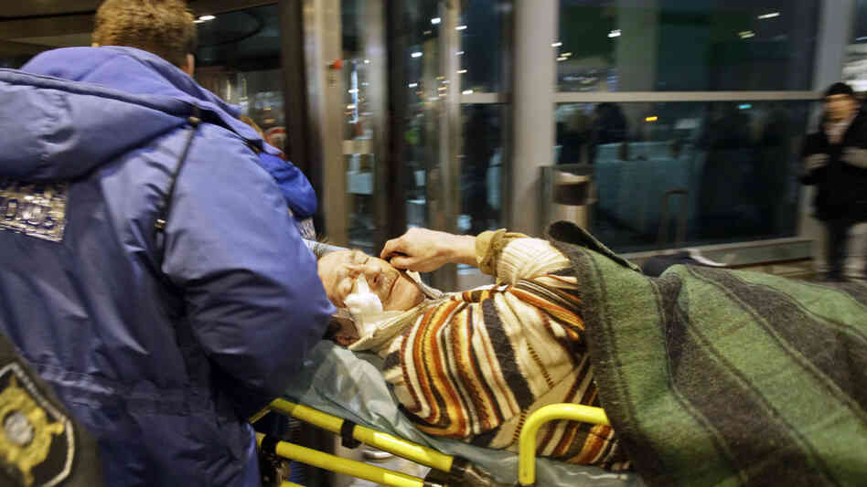 Emergency personnel tend to a man wounded in the explosion Monday at Domodedovo Airport in Moscow.