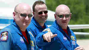 May 28, 2008, file photo: Space shuttle Discovery commander Mark Kelly, right, gestures as he walks with his twin brother astronaut Scott Kelly, left, and mission specialist Ron Garan, after arrival at Kennedy Space Center in Cape Canaveral, Fla.