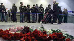 While some people wait in a line, a woman pushes her luggage past flowers at Domodedovo airport near Moscow earlier today (Jan. 25, 2011).