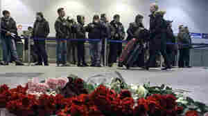 A woman pushes her luggage past an array of flowers laid out a day after the deadly explosion at Domodedovo Airport near Moscow as people wait in line for a security check.