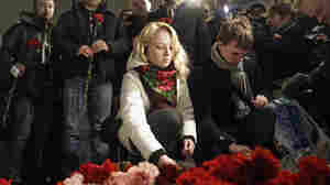 People place flowers at the site of the blast at Domodedovo Airport on Tuesday as others wait for a security check to enter. Security was tightened after an explosion ripped through Moscow's busiest airport Monday.