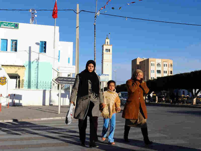 People walk in the street in Sidi Bouzid on Jan. 10.