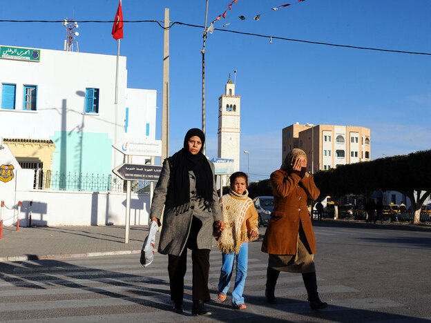 People walk in the street in Sidi Bouzid on Jan. 10.