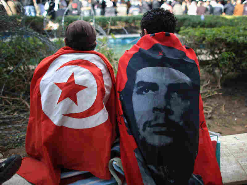 Protesters draped in flags rest outside the Tunisian prime minister's office in Tunis, Tunisia.