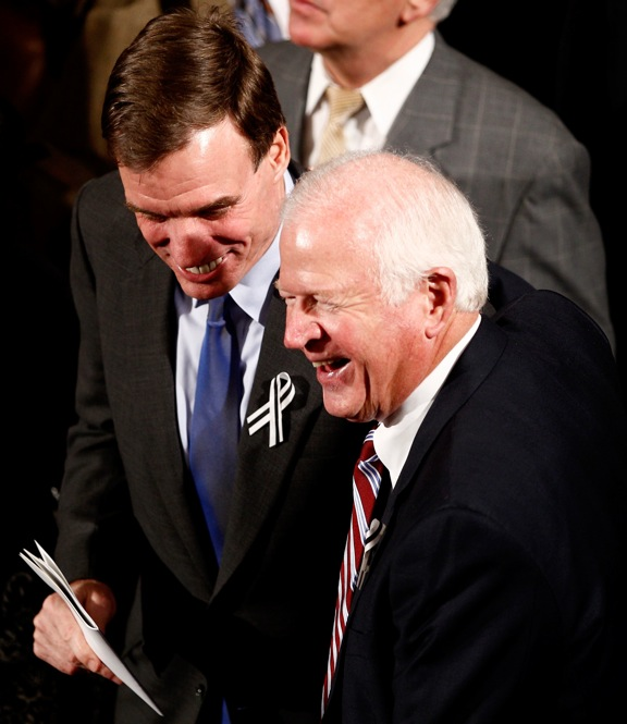 Sen. Mark Warner (D-VA), left, and Sen. Saxby Chambliss (R-GA), share a laugh as they prepare to sit together.