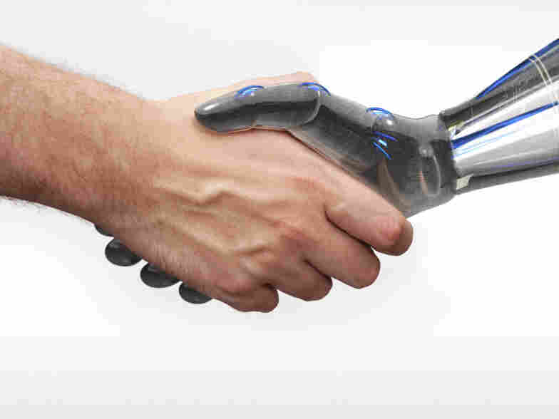 A human and robot shake hands
