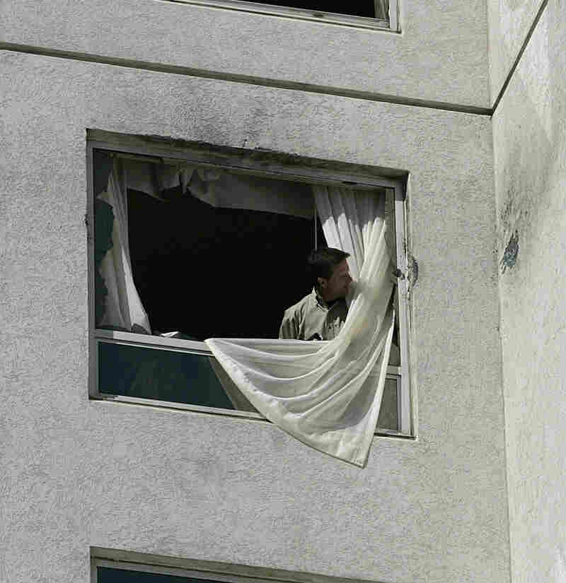 An unidentified man looks at the damage to a window at Harrah's hotel-casino, after police blasted out the 20th-story window and stormed the room. Authorities say the suspect killed another man and shot at police and paramedics during a six-hour standoff.